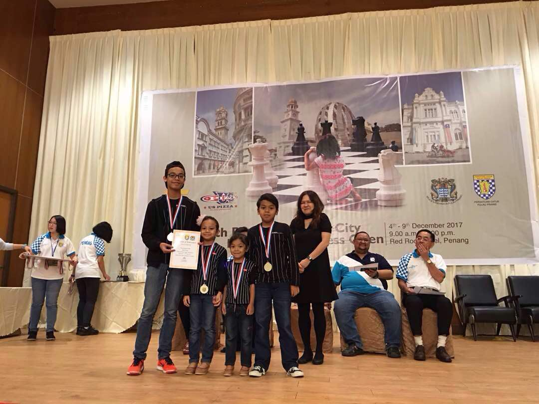 Four-year and six months old Ain Safiya with the rest of Team AAAA, accepting the prize of Best Family Team at the Chess League Team Tournament (Photo by Penang Chess Association)