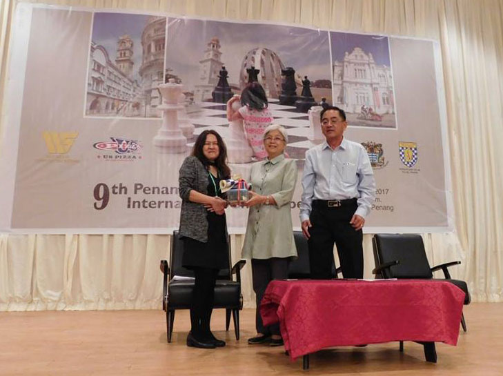 President of Penang Chess Association, Madam See Swee Sie (left) presenting a token of appreciation to Y.B. Chong Eng (centre). Looking on is the immediate past President of Penang Chess Association, Mr. Lee Ewe Gee (Photo by Penang Chess Association)