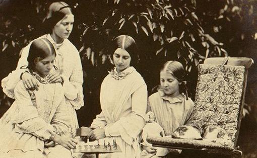 """Fanny, Maria, Joanna y Anne Smithin jugando al ajedrez en el jardín de Dinsdale Rectory, Yorkshire (¿con Kitty, la gata a la queAlicia le dijo: """"Hace un rato, cuando jugábamos, mirabas como si entendieras. Y cuando dije «¡Jaque!», ronroneaste…""""?)."""