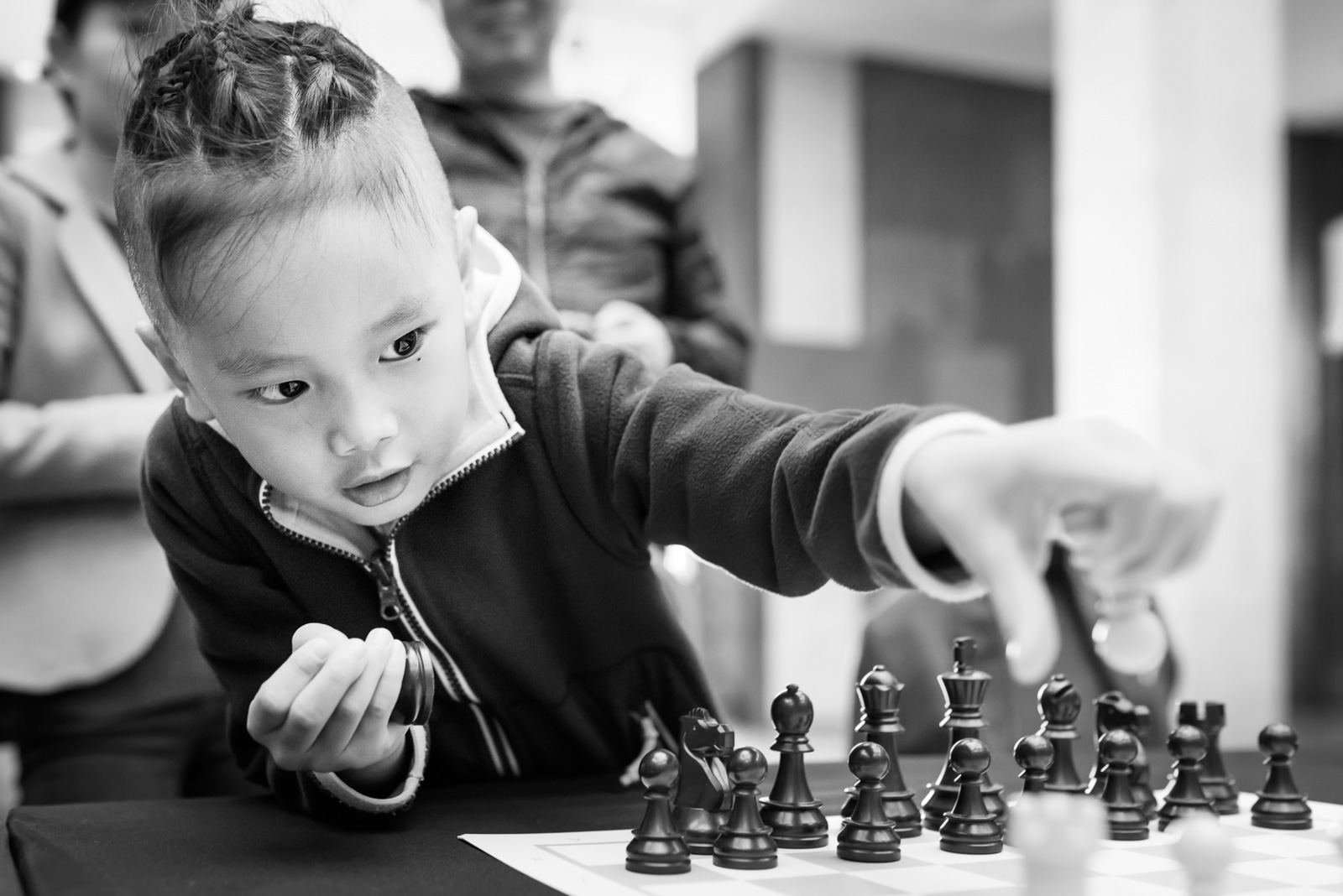 girl reaches across chess board